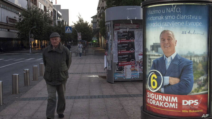 "A man walks by an election poster of pro-Western Prime Minister Milo Djukanovic, leader of the Democratic Party of Socialists, reading ""We are joining NATO, we are at the doorstep at the developed European family"" and ""With firm step ahead!"" in downt"