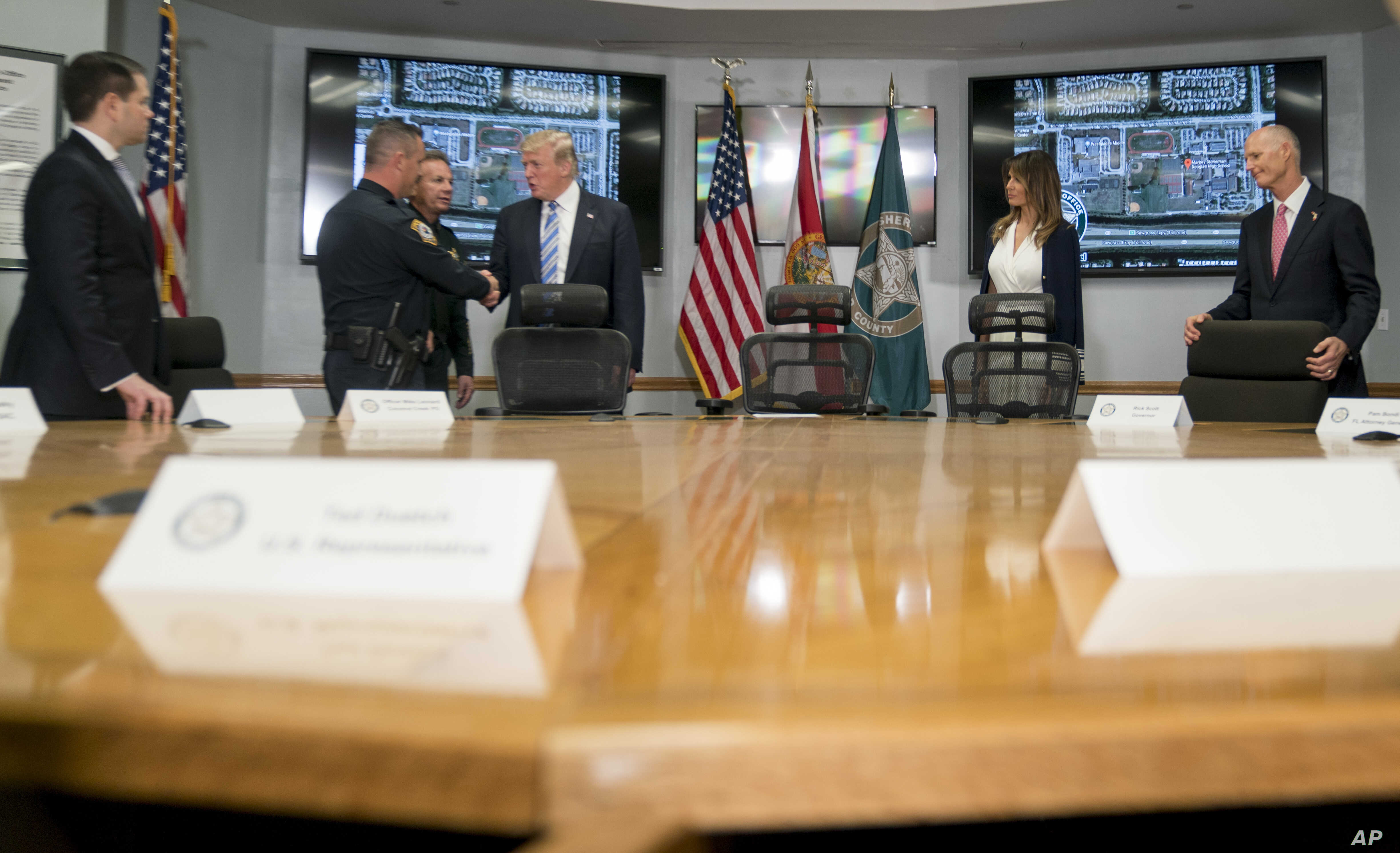 President Donald Trump, third from right, shakes hands with Coconut Creek Police Officer Mike Leonard, second from left, as he meets with law enforcement officers at Broward County Sheriff's Office in Pompano Beach, Fla., Feb. 16, 2018, following the