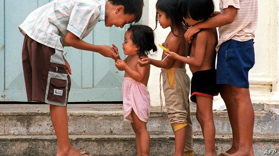 FILE - Cambodian orphans play together as they wait for adoption at an orphanage in Phnom Penh, June 22, 2000.