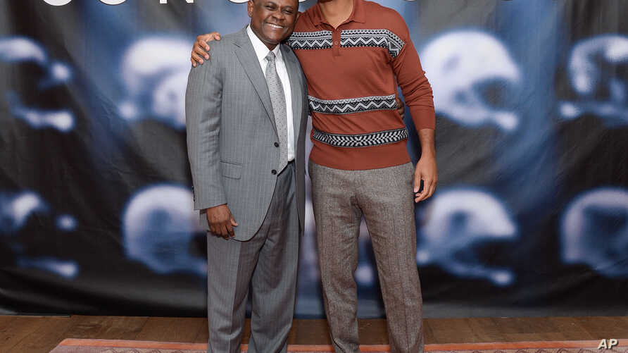 """FILE - In this Dec. 14, 2015, file photo, Dr. Bennet Omalu, left, and actor Will Smith pose together at the cast photo call for the film """"Concussion"""" at The Crosby Street Hotel in New York. The movie releases in U.S. theaters on Dec. 25, 2015."""