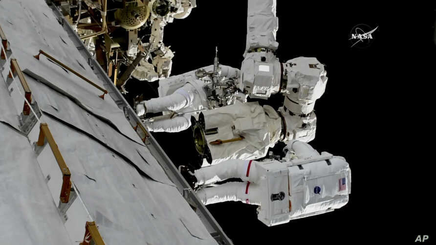 In this frame from NASA TV, Astronauts Mark Vande Hei and Randy Bresnik, bottom, work on the International Space Station, Oct. 5, 2017.