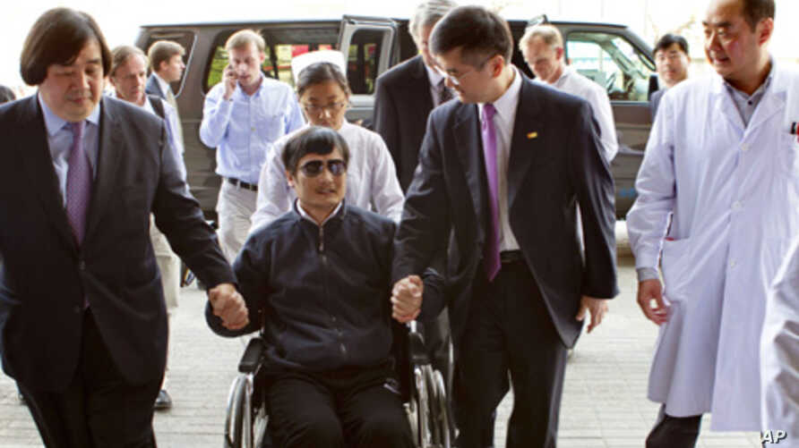 In this photo released by the U.S. Embassy Beijing Press Office, blind lawyer Chen Guangcheng is wheeled into a hospital by U.S. Ambassador to China Gary Locke, right, and an unidentified official at left, in Beijing, May 2, 2012.