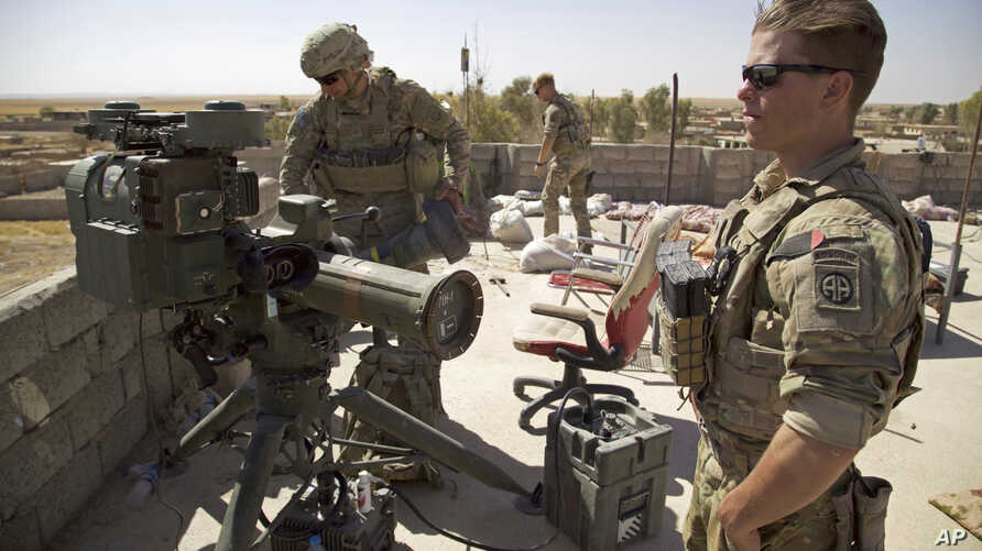 FILE - In this Aug. 20, 2017 file photo, U.S. Army soldiers stands next to a guided-missile launcher, a few miles from the frontline, in the village of Abu Ghaddur, east of Tal Afar, Iraq.
