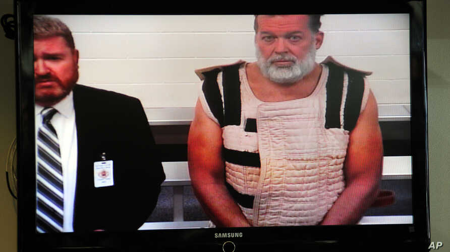 Colorado Springs shooting suspect, Robert Dear, right, appears via video before Judge Gilbert Martinez, with public defender Dan King, at the El Paso County Criminal Justice Center for this first court appearance, where he was told he faces first deg
