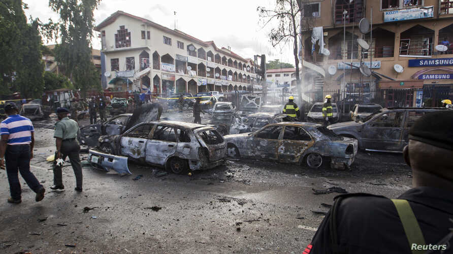 Burnt-out cars are seen at the scene of a blast in Abuja, June 25, 2014. At least 21 people were killed when a suspected bomb tore through a crowded shopping district in the Nigerian capital Abuja during rush hour on Wednesday, police said, adding to