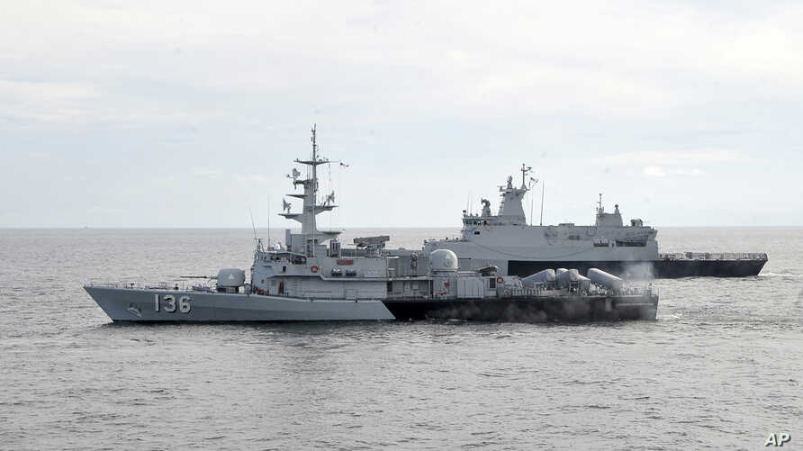 A Royal Malaysian Navy's missile corvette and an offshore patrol vessel are seen during a search and rescue operation for the missing Malaysia Airliner over the Straits of Malacca, Malaysia, March 13, 2014.