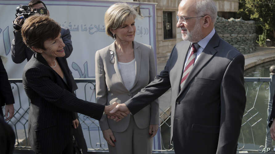 Iraqi Foreign Minister Ibrahim al-Jaafari, right, shakes hands with the Australian Ambassador to Iraq Lyndall Sachs, as Australian Foreign Minister Julie Bishop looks on in Baghdad, Iraq, Saturday, Oct. 18, 2014.