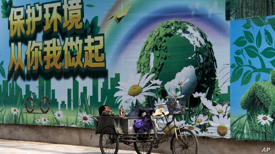 "A migrant worker listens to radio on his tricycle cart parked next to a billboard promoting environment protection with the slogan ""Environment protection starts from you and me"" on display at the Central Business District of Beijing, June 5, 2017."