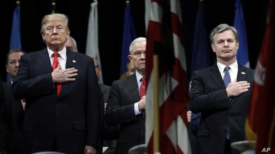 FILE - President Donald Trump, Attorney General Jeff Sessions, center and FBI Director Christopher Wray stand during the National Anthem at the FBI National Academy graduation ceremony in Quantico, Va.