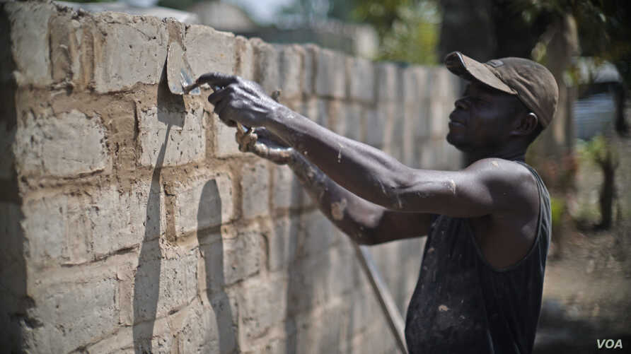 A Central African Republic man works to reconstruct a home in the PK5 neighborhood of Bangui in February 2017. (Z. Baddorf/VOA)