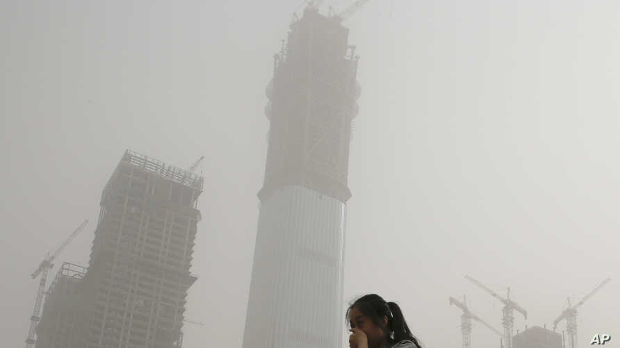 A woman covers her face with her hands to protect her from polluted air and a sandstorm in Beijing, May 4, 2017. Authorities in Beijing issued a blue alert on air pollution as sandstorm swept through the Chinese capital city on Thursday morning.