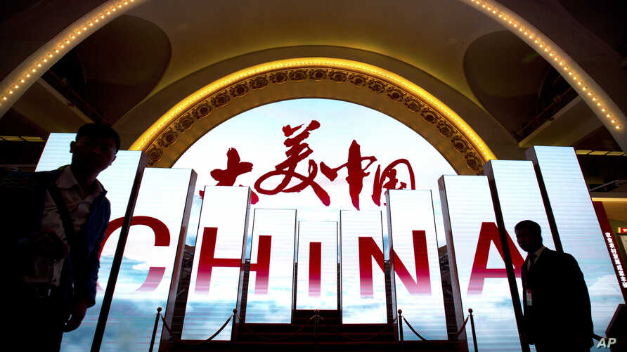 FILE - Visitors walk past video display boards at an exhibition highlighting China's achievements under five years of leadership by Chinese President Xi Jinping at the Beijing Exhibition Hall in Beijing, Sept. 28, 2017.