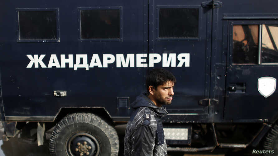 FILE - A man walks in front of a police truck in a Roma neighborhood in the city of Pazadzhik, Bulgaria, Nov. 25, 2014.