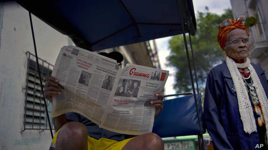 FILE - In this Feb. 3, 2015 file photo, a man reads a copy of the official newspaper of the Central Committee of the Cuban Communist Party, Granma, as a woman walks past, in old Havana.