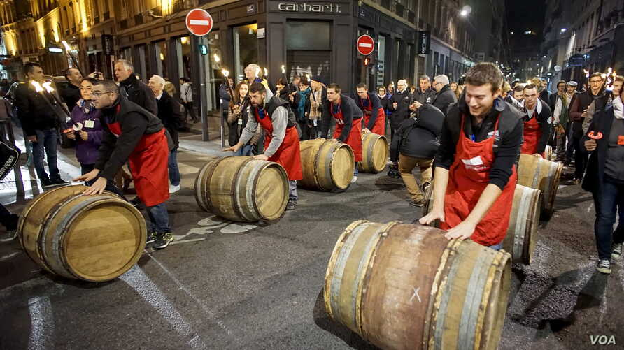 Men roll barrels of Beaujolais Nouveau wine for the official launch of the 2015 vintage in the center of Lyon early November 19, 2015.