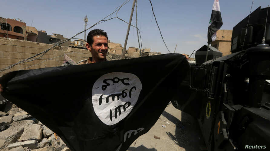A member of Iraqi Counter Terrorism Service holds an Islamic State militants as he celebrates in the Old City of Mosul, Iraq July 9, 2017.