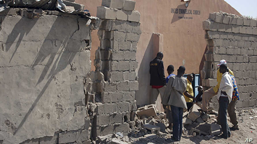 People stand near a damaged wall of a church after an explosion in Jajeri district in Nigeria's northeastern city of Maiduguri, December 23, 2011