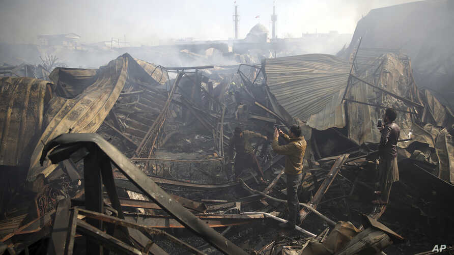 Men take photos of the ruins left after a fire devastated an electronic appliances market in Kabul, Afghanistan, Nov. 2, 2018. Residents of the Afghan capital are grappling with the aftermath of a massive blaze that destroyed hundreds of stores at a