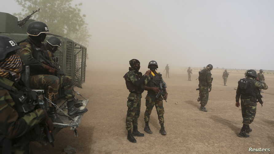 Cameroonian soldiers from the Rapid Intervention Brigade stand guard amidst dust kicked up by a helicopter in Kolofata, Cameroon, March 16, 2016.