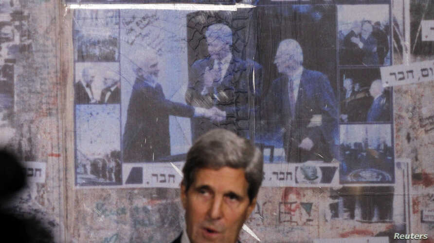 U.S. Secretary of State John Kerry is pictured in front of a photo (L-R) showing Jordan's former King Hussein, former U.S. President Bill Clinton and Israel's former Prime Minister Yitzhak Rabin, as Kerry marks the 18th anniversary of Rabin's assassi