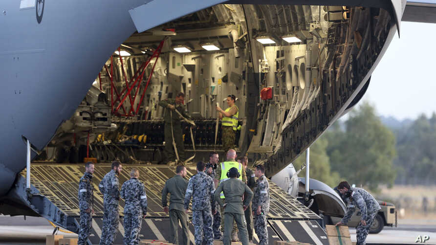 Ground crew prepare to unload a Sea Hawk helicopter from a Royal Australia Air Force C-17 after it landed at RAAF Base Pearce to help with the search for the missing Malaysia Airlines Flight MH370 in Perth, Australia, March 28, 2014.