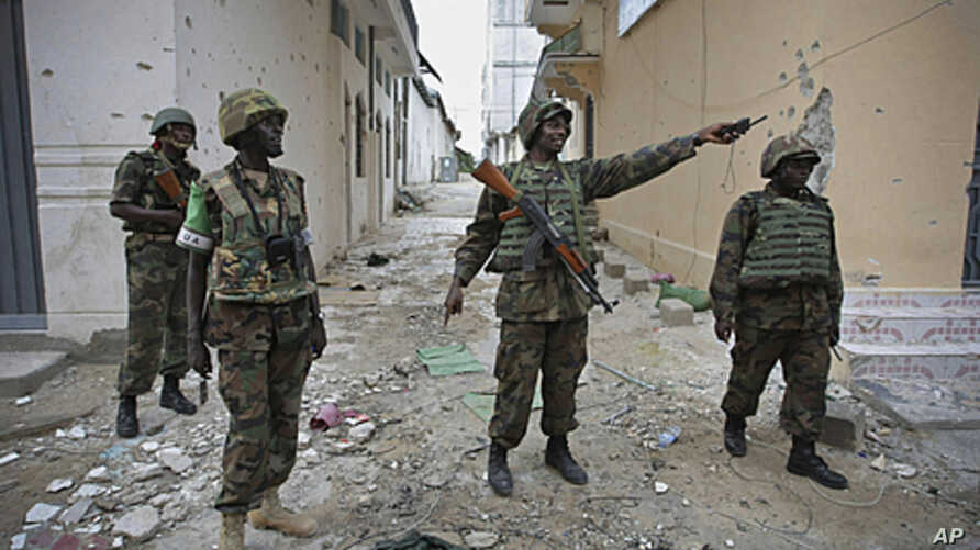In this photo released by the African Union-United Nations Information Support Team, Ugandan soldiers serving with AMISOM patrol through the deserted streets of Bakara Market in central Mogadishu, August 9, 2011 (file photo)