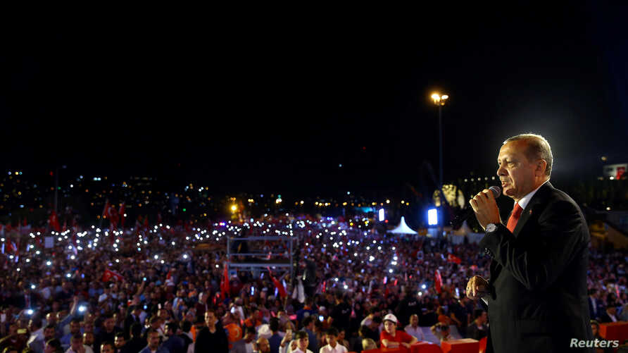 Turkish President Recep Tayyip Erdogan addresses his supporters during a ceremony marking the first anniversary of an attempted coup at the Bosporus Bridge in Istanbul, July 15, 2017.