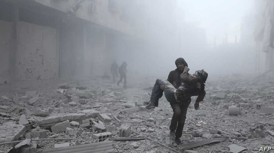A wounded man is carried following an air strike on the rebel-held besieged town of Arbin, in the eastern Ghouta region on the outskirts of the capital Damascus on January 2, 2018.