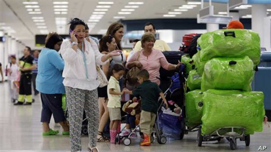 Passengers wait in line for a flight departing to Cuba at Miami International Airport in Miami, Florida, September 27, 2012.
