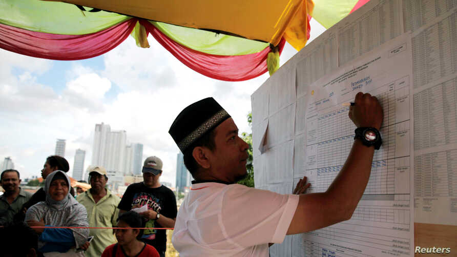 An election official counts votes during an election for Jakarta's governor in Jakarta, Indonesia, Feb. 15, 2017.