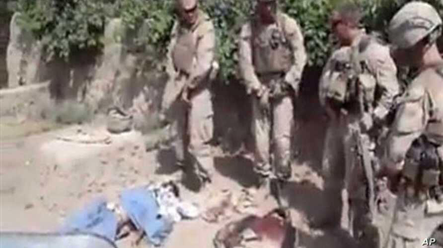 """This image made on Thursday, Jan. 12, 2012 from undated video posted on the Internet on Wednesday, Jan. 11, 2012 by a YouTube user who identified self as """"semperfiLoneVoice"""" shows men in U.S. Marine combat gear, standing in a semi-circle over three b"""