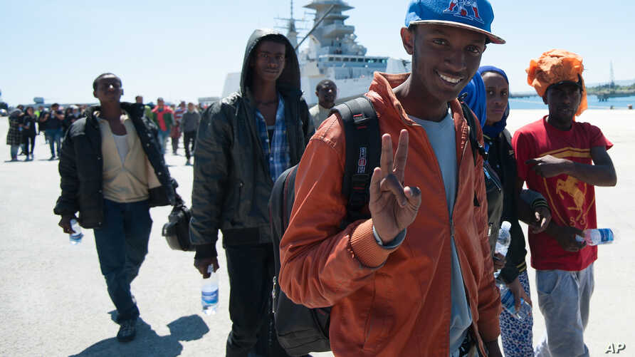"A rescued migrant shows the victory sign after disembarking from the Italian Navy vessel ""Bettica"" at Augusta, Sicily, southern Italy, April 22, 2015."