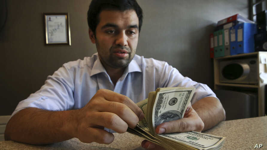 FILE-- An Iranian currency exchange bureau worker counts U.S. dollars in Tehran, April 5, 2015. In January 2016, Iran transferred some of the billions in frozen overseas assets following the implementation of the nuclear deal with world powers.