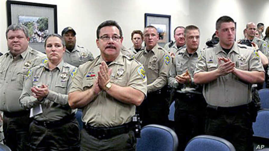 Maricopa County Sheriff's Office jail officers, who lost their federal power to check whether inmates are in the county illegally, give Sheriff Joe Arpaio a standing ovation after they turned in their credentials when federal officials pulled the She