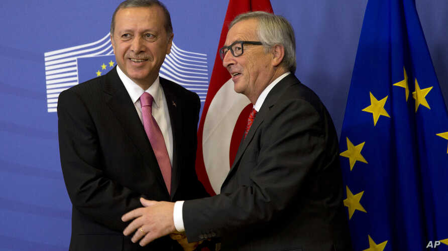 Turkish President Recep Tayyip Erdogan, left, is greeted by European Commission President Jean-Claude Juncker prior to a meeting at EU headquarters in Brussels, Belgium, Oct. 5, 2015.