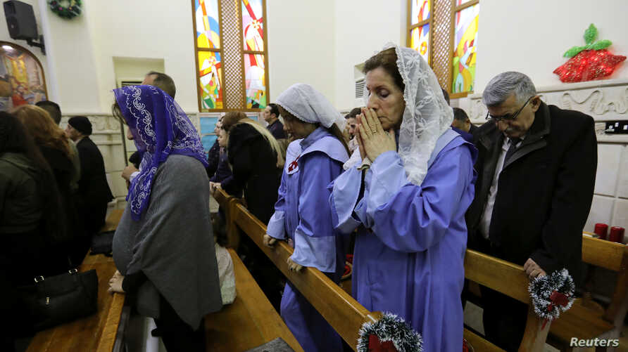 Iraqi Christians pray during a mass on Christmas at St George Chaldean Catholic Church in Baghdad, Iraq, Dec. 25, 2018.