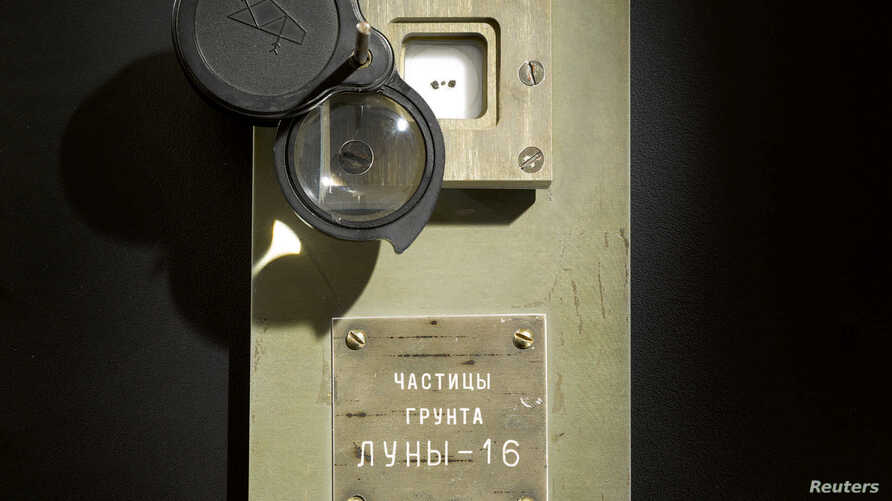 Three lunar samples, which Sotheby's says are the only known documented moon rocks in private hands, from the unmanned Soviet Luna-16 Mission in 1970 which returned to Earth, are shown encased under glass below an adjustable lens, in this photo taken