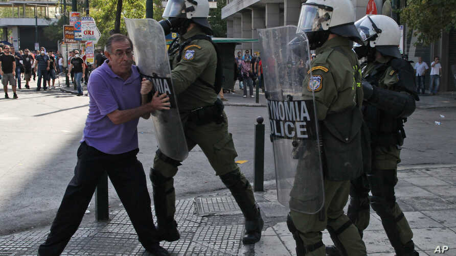 A riot policeman pushes an elderly protester with his shield during clashes during the 24-hour nationwide general strike in Athens, October 18, 2012.