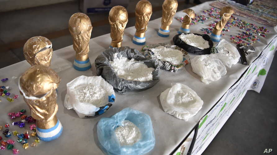 This June 21, 2018, photo, released by the National Security Ministry, shows fake World Cup trophies stuffed with cocaine, and the product itself on display next to the trophies, in Buenos Aires, Argentina.