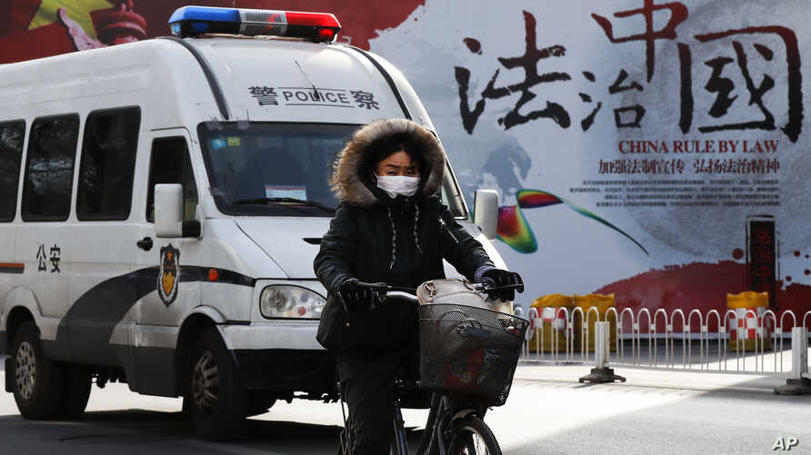 """A woman and a police van pass a Chinese government propaganda billboard that reads """"China Rule By Law"""" on a street in Beijing, Dec. 28, 2016. Infuriated by a decision by Beijing prosecutors to drop charges in a high-profile police brutality case, uni"""