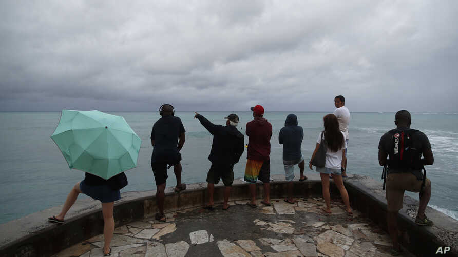 People look out over the ocean along Waikiki Beach in a light rain from Tropical Storm Lane, Aug. 25, 2018, in Honolulu.