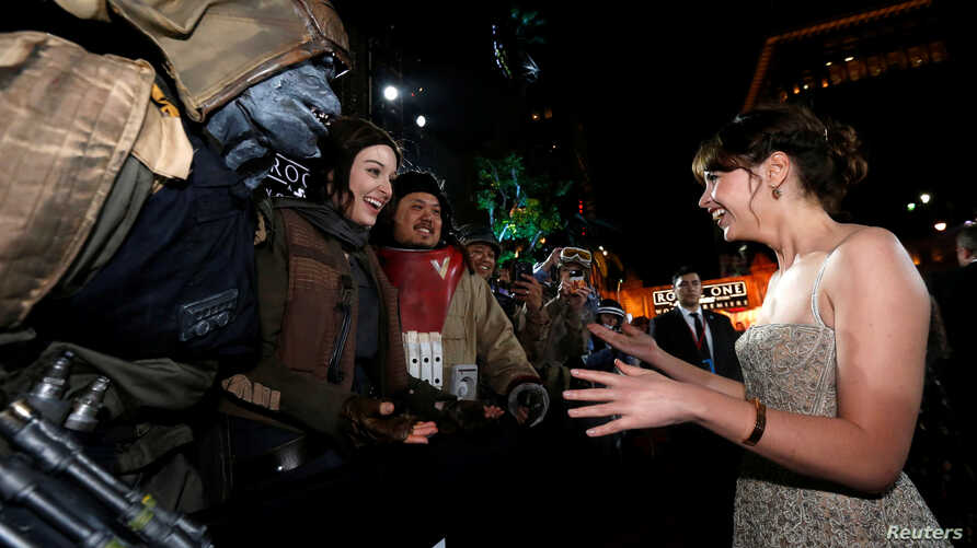 """FILE - Actress Felicity Jones chats with fans as she arrives at the world premiere of the film """"Rogue One: A Star Wars Story"""" in Hollywood, California, U.S., Dec. 10, 2016."""