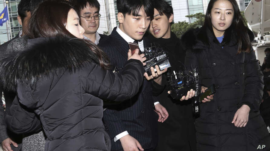 Seungri, center, member of a popular K-pop boy band Big Bang, arrives at the Seoul Metropolitan Police Agency in Seoul, South Korea, March 14, 2019.