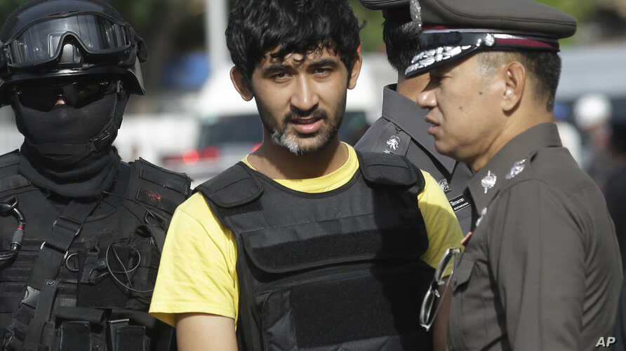 Police officers escort a key suspect in last month's Bangkok bombing, yellow shirt, identified by Thai police as Yusufu Mierili, also as Yusufu Mieraili, traveling on a Chinese passport, but his nationality remains unconfirmed, outside Hua Lamphong r