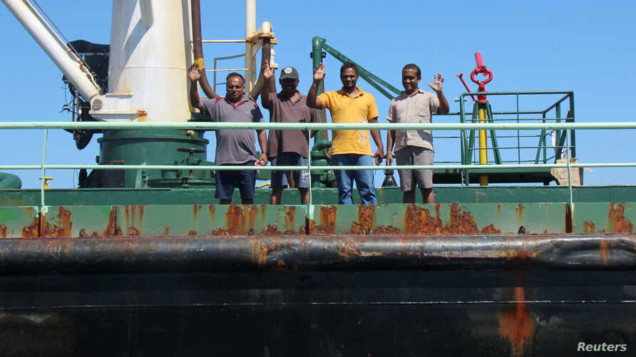 FILE - Crew members wave aboard oil tanker Aris-13, which was released by pirates, as it sails to dock on the shores of the Gulf of Aden, northern Somalia's semi-autonomous region of Puntland, March 19, 2017.