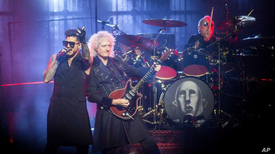 FILE - US singer Adam Lambert performs with British guitarist Brian May (end-R) and drummer Roger Taylor from British rock band Queen during their concert in Papp Laszlo Budapest Sports Arena in Budapest, Hungary, Nov. 4, 2017.