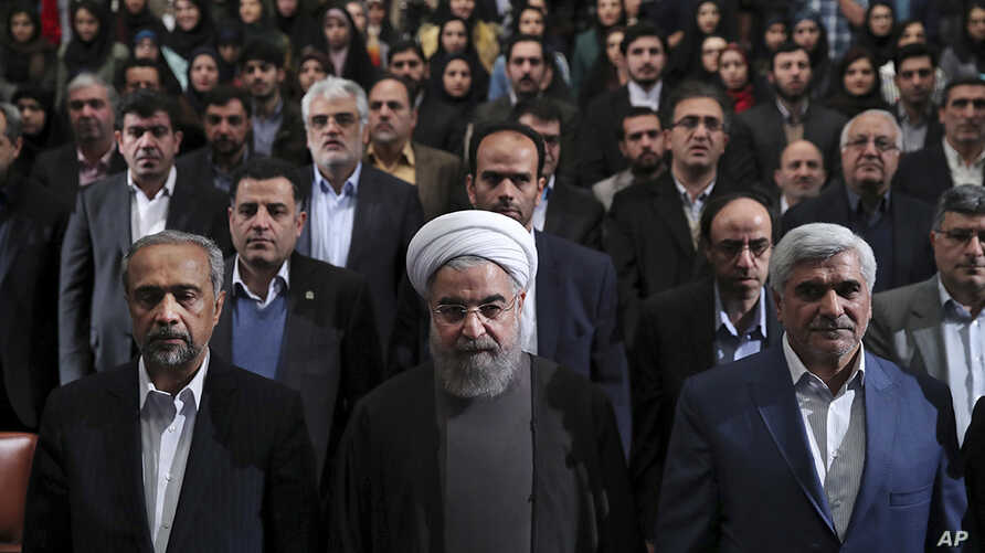 In this photo released by official website of the office of the Iranian Presidency, President Hassan Rouhani, center, Science Minister Mohammad Farhadi, right, and head of the President's office Mohammad Nahavandian, left, listen to the national anth