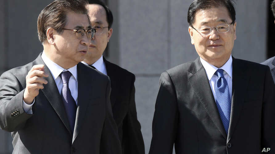 South Korea's national security director Chung Eui-yong, right, and National Intelligence Service Chief Suh Hoon, left, talk before boarding an aircraft as they leave for Pyongyang at a military airport in Seongnam, south of Seoul, March 5, 2018.