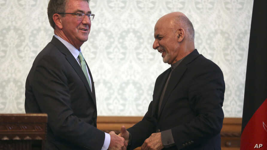 Afghan President Ashraf Ghani, right, shakes hands with U.S. Defense Secretary Ash Carter, left, after a press conference at presidential palace in Kabul, Afghanistan, Dec. 9, 2016.