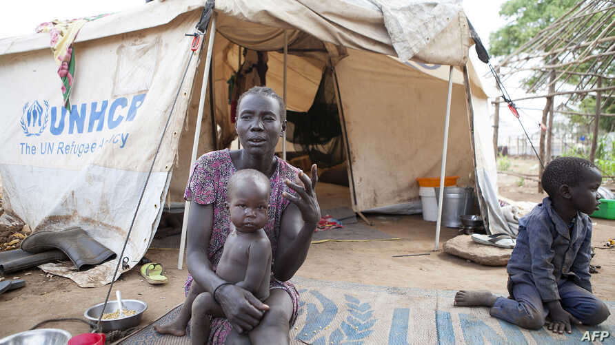 A woman and her children displaced by fighting in South Sudan sit outside her tent at the Kule camp for Internally Displaced People at the Pagak border crossing in Gambella, Ethiopia, July 10, 2014.